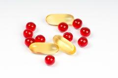 Vitamin e och kapslar för olja för torsklever Arkivbild