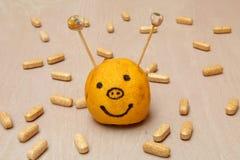 Vitamin ergänzt das Umgeben eines smiley, der von einer Zitrone gemacht wird Lizenzfreie Stockbilder