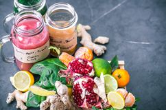 Vitamin fresh fruit smoothies in glass jars with fruit. Vitamin fresh smoothies in glass jars with fruits on a black beautiful background Royalty Free Stock Image