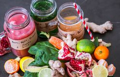Vitamin fresh fruit smoothies in glass jars with fruit. Vitamin fresh smoothies in glass jars with fruits on a black beautiful background Royalty Free Stock Photo