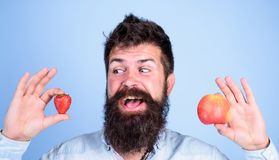 Vitamin fruit nutrition concept. Healthcare dieting vitamin. Fruit and berry in hands healthy alternative. Fruits or. Berries Man bearded smiling holds apple stock photography