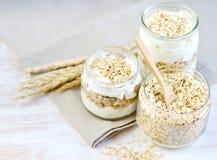 Vitamin-gesunder Frühstücks-Jogurt mit Hafer-Flocken-Weiß-hölzernem Hintergrund lizenzfreie stockbilder