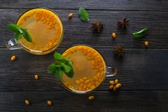 Vitamin healthy sea buckthorn tea in glass cups with fresh raw sea buckthorn berries and cinnamon sticks, anise stars, mint. And honey on a dark kitchen table Stock Images