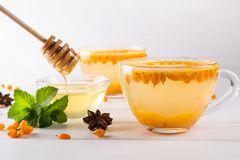 Vitamin healthy sea buckthorn tea in glass cups with fresh raw sea buckthorn berries and cinnamon sticks, anise stars, mint. And honey on a white kitchen table Stock Photography