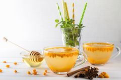 Vitamin healthy sea buckthorn tea in glass cups with fresh raw sea buckthorn berries and cinnamon sticks, anise stars, mint  and h. Oney on a white kitchen table Royalty Free Stock Images