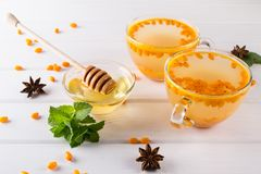 Vitamin healthy sea buckthorn tea in glass cups with fresh raw sea buckthorn berries. And cinnamon sticks, anise stars, mint  and honey on a white kitchen table Stock Photography