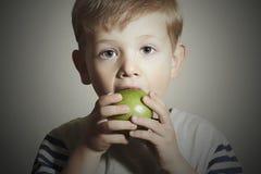 vitamin Kind, das Apple isst Little Boy mit grünem Apfel Biokost Corn Flakes Früchte Stockfotografie