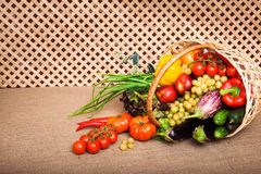 Vitamin mix in the wicker basket. Vitamin mixture of fresh vegetables, fruits and lettuce in wicker basket on kitchen table, covered Sack cloth on a background royalty free stock photos