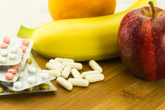 Vitamin pills and various fruits Royalty Free Stock Photography