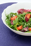 Vitamin salad with arugula cherry tomatoes and sesame. Arugula, sesame and cherry tomatoes with olive oil close-up Royalty Free Stock Photo