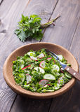 Vitamin salad of wild herbs with cucumber, radish and green onions. In a wooden bowl on a wooden background. Healthy detox diet food royalty free stock image