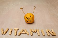 Vitamin sign created from vitamin pills in front of a smiley Royalty Free Stock Image