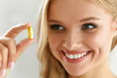 Vitamin And Supplement. Beautiful Woman Holding Fish Oil Capsule Stock Photography