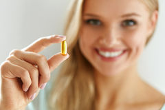 Vitamin And Supplement. Beautiful Woman Holding Fish Oil Capsule. Vitamin And Supplement. Beautiful Smiling Woman Holding Fish Oil Capsule In Hand. Portrait Of Royalty Free Stock Photo