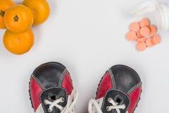 Vitamina C Fruta cítrica natural y tabletas sintéticas, opción Fondo blanco, zapatillas de deporte del ` s de los niños foto de archivo libre de regalías
