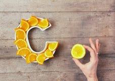 Vitamina C ou nutriente ácido ascórbico no conceito do alimento Placa na forma da letra C com fatias alaranjadas e da mão da mulh fotos de stock royalty free