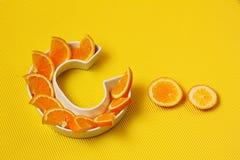 Vitamina C ou nutriente ácido ascórbico no conceito do alimento Placa na forma da letra C com fatias alaranjadas no fundo amarelo imagens de stock royalty free