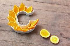 Vitamina C ou nutriente ácido ascórbico no conceito do alimento Placa na forma da letra C com fatias alaranjadas no fundo de made foto de stock royalty free