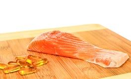 Vitamina D con il salmone su fondo bianco fotografie stock