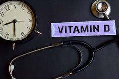 Vitamina D en el papel con la inspiración del concepto de la atención sanitaria despertador, estetoscopio negro imagen de archivo