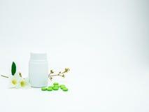 A vitamina e o suplemento marcam comprimidos com flor e ramo e anulam a garrafa plástica da etiqueta no fundo branco com espaço d foto de stock royalty free