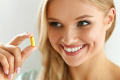 Vitamina e suplemento Mulher bonita que guarda a cápsula do óleo de peixes imagem de stock