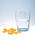 Vitaminas con el vidrio de agua Fotos de archivo libres de regalías