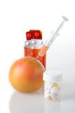 Vitaminas de píldoras y de la fruta Foto de archivo