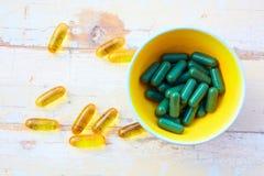 Vitaminas del petróleo de pescados y píldoras herbarias Foto de archivo libre de regalías