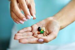 Vitaminas e suplementos Mão fêmea que guarda comprimidos coloridos imagem de stock