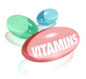 Vitaminas en el fondo y la palabra blancos en cápsula Fotografía de archivo libre de regalías