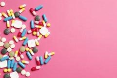 vitaminas Multi-coloridas em um fundo cor-de-rosa imagem de stock