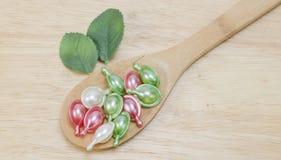 Vitaminas naturales para la buena salud en una cuchara de madera en un fondo de madera Fotografía de archivo
