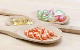 Vitaminas naturales para la buena salud en una cuchara de madera en un fondo de madera Imagen de archivo libre de regalías