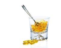 Vitaminas Omega-3 en vidrio y cucharilla imagen de archivo