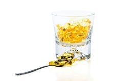 Vitaminas Omega-3 en vidrio y cucharilla imagenes de archivo