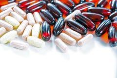 Vitaminas, Omega 3, aceite de hígado de bacalao, suplemento dietético y tabletas un terraplén en un cierre ligero del fondo para  Foto de archivo libre de regalías