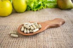Vitaminas sintéticas ou naturais Cápsulas do vegetariano em s de madeira marrom fotografia de stock royalty free
