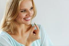 Vitaminas y suplementos de la comida Mujer hermosa con la píldora a disposición imágenes de archivo libres de regalías