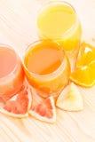 Vitaminbakgrund Nya frukter med exponeringsglas av fruktsaft bakom Royaltyfri Bild
