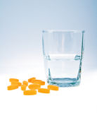Vitamine con vetro di acqua Fotografie Stock Libere da Diritti