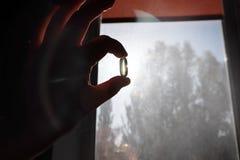 Vitamine D ou Omega 3 capsules Gel de vitamine à disposition contre la fenêtre Le concept d'un manque de vitamine D dans le corps image stock
