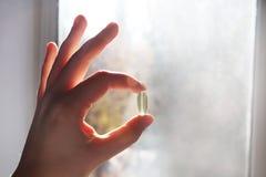 Vitamine D ou Omega 3 capsules Gel de vitamine à disposition contre la fenêtre Le concept d'un manque de vitamine D dans le corps photographie stock