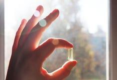 Vitamine D ou Omega 3 capsules Gel de vitamine à disposition contre la fenêtre Le concept d'un manque de vitamine D dans le corps image libre de droits