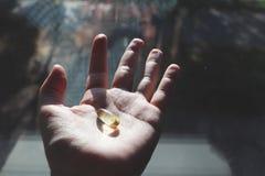 Vitamine D ou Omega 3 capsules Gel de vitamine à disposition contre la fenêtre Le concept d'un manque de vitamine D dans le corps photos stock