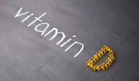 Vitamine de Word et pilules jaunes formant la forme à l'alphabet de D sur le fond en bois photos libres de droits