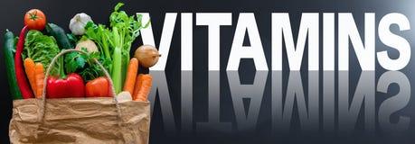 VITAMINE di parola contro fondo scuro con le verdure organiche sane fresche nel sacco di carta fotografie stock libere da diritti