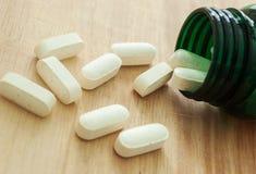 Vitamine die uit een fles morsen Stock Afbeeldingen