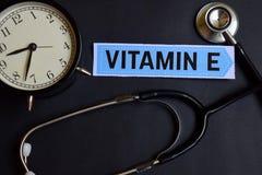 Vitamine E op het document met de Inspiratie van het Gezondheidszorgconcept wekker, Zwarte stethoscoop royalty-vrije stock fotografie