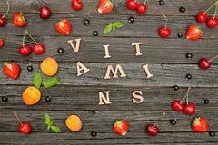 Vitamine Früchte und Buchstaben auf einem schwarzen hölzernen Hintergrund, Lebensmittelkonzept stockfotografie